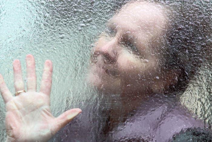 Anciana detrás de vidrio